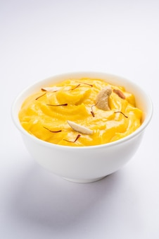Amrakhand est un yogourt ou shrikhand aromatisé alphonso, un bonbon indien populaire servi avec des fruits secs et du safran avec des mangues entières, sur fond coloré. mise au point sélective