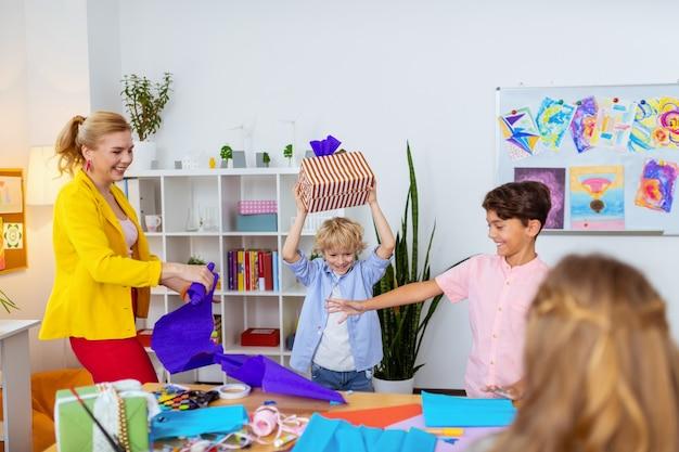 Amusant après la décoration. les garçons et l'enseignant s'amusent beaucoup après avoir décoré ensemble des boîtes à cadeaux