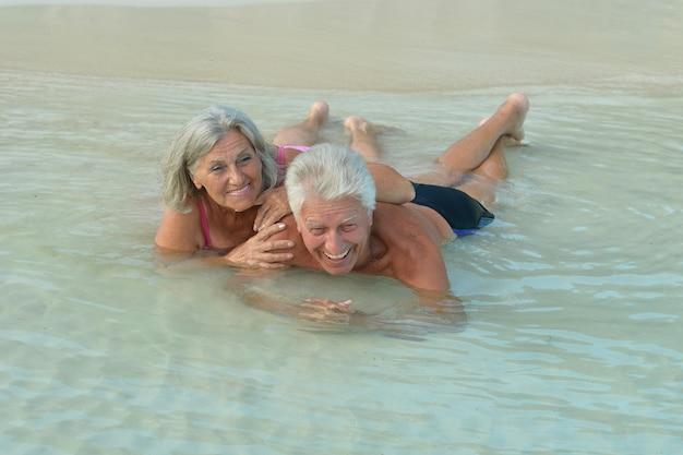 Amusant couple de personnes âgées se reposant sur la plage