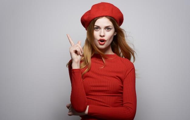 Amusant geste de la main jolie femme lèvres rouges studio de luxe posant. photo de haute qualité