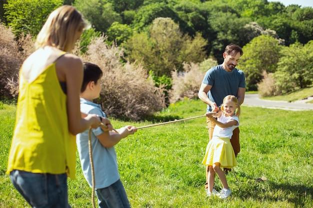 Amusant. heureux père aimant aidant sa fille pendant qu'elle tirait une corde avec son frère