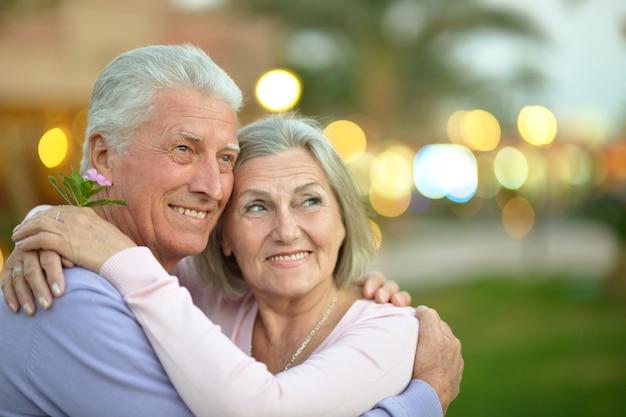 Amusant heureux vieux couple souriant avec fleur