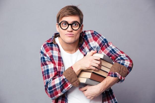 Amusant jeune homme comique à lunettes rondes et chemise à carreaux tenant des livres sur un mur gris