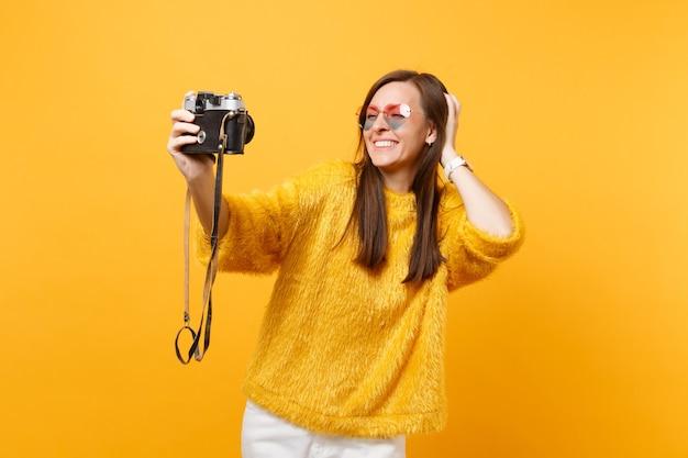 Amusante jeune femme à lunettes coeur faisant prise de selfie sur appareil photo vintage rétro, mettant la main sur la tête isolée sur fond jaune. les gens émotions sincères, mode de vie. espace publicitaire.