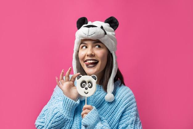 Amusante jeune fille debout avec une délicieuse sucette panda à la main et un chapeau sur la tête sur fond rose.