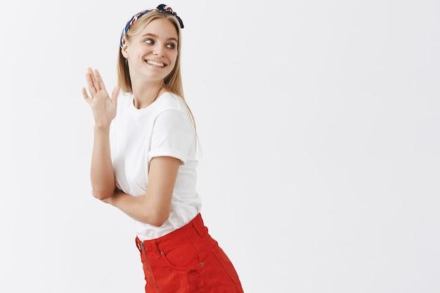 Amusé coquette jeune fille blonde posant contre le mur blanc