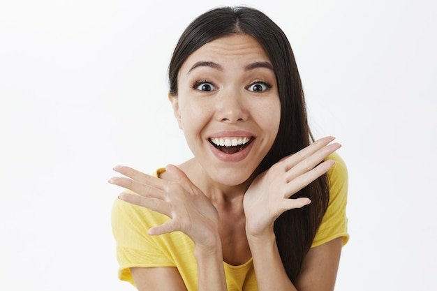 Amusé et excité femme enthousiaste heureuse aux cheveux noirs en t-shirt jaune tenant des paumes près du visage
