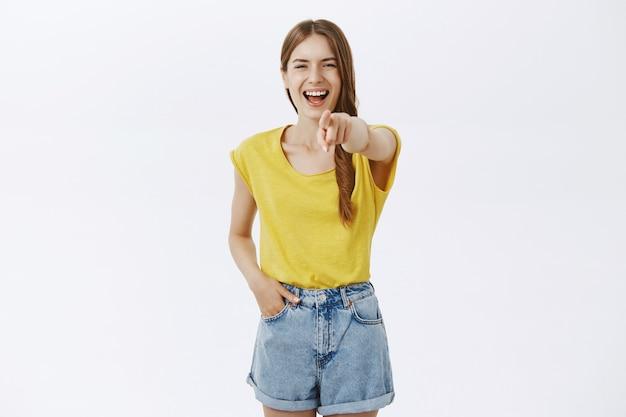 Amusé heureux jeune fille bénéficiant d'un spectacle drôle, pointer du doigt et rire