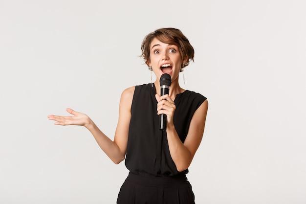 Amusée belle femme chantant karaoké, tenant le microphone, debout sur blanc.