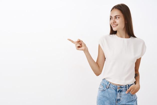 Amusée curieuse jolie et élégante femme caucasienne en chemisier blanc tenant la main dans la poche de jeans tournant et pointant vers la gauche avec intérêt souriant joyeusement en se tenant debout sur un mur gris