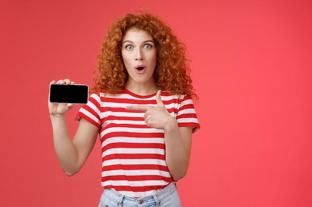 Amusée fascinée mignonne fille bouclée rousse adore jouer à des jeux tenir le smartphone horizontal montrer le pouce vers le haut bouche ouverte haletant étonné heureux joyeusement présent propre score application préférée fond rouge.