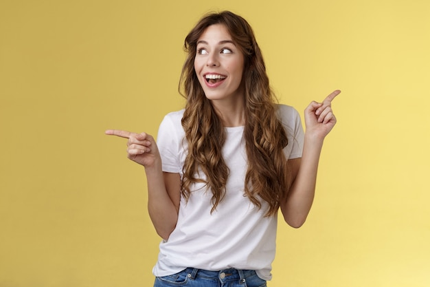 Amusée joyeuse souriante heureuse jeune femme aux cheveux bouclés, les cheveux châtains observent curieusement l'espace de copie souriant admiration joie pointant sur le côté faisant le choix impressionné satisfait tourner à gauche.