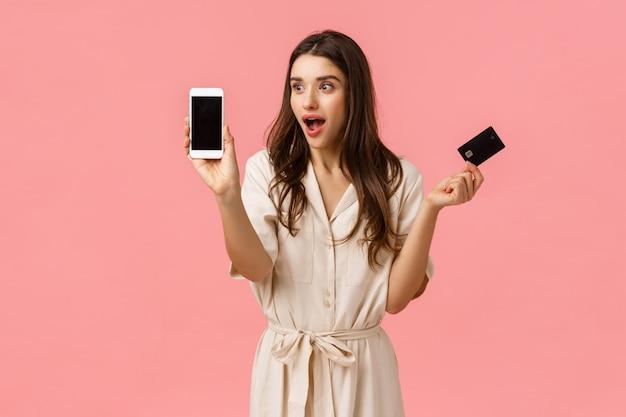 Amusée et surprise, belle femme de race blanche en robe, tenant une carte de crédit et montrant quelque chose d'étourdissant et cool à l'écran du téléphone, debout rose mur joyeux
