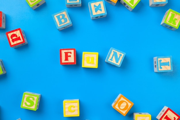 Amusement. blocs d'alphabet coloré en bois sur bleu
