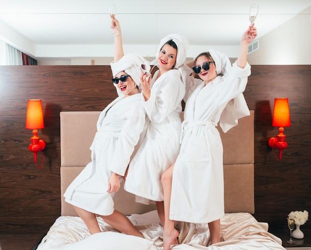 Amusement et détente bff. les femmes souriantes avec du champagne sur le lit. lunettes de soleil, peignoirs et turbans serviettes.