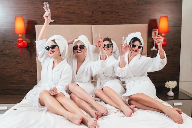 Amusement de partie de bachelorette. femelles souriantes avec champagne. acclamations. lunettes de soleil, peignoirs et turbans sur. jambes nues.