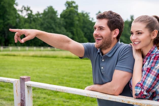 Amusement de ranch. vue latérale d'un jeune couple d'amoureux heureux se tenant près l'un de l'autre et souriant tandis que l'homme pointe du doigt