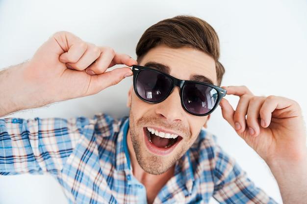 Amusement sans soucis. vue de dessus du jeune homme gai ajustant les lunettes