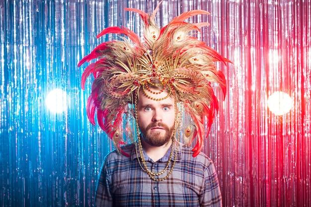 Amusement, vacances et concept de personnes de jour de poisson d'avril - homme étrange avec masque et chapeau de carnaval