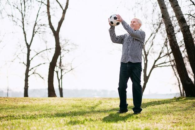 Amusez-vous avec le ballon. homme d'âge mûr positif exerçant avec ballon et debout sur l'herbe