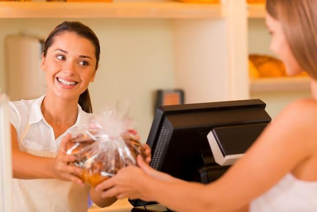 Amusez-vous! belle jeune boulangère donnant des biscuits au client et souriant