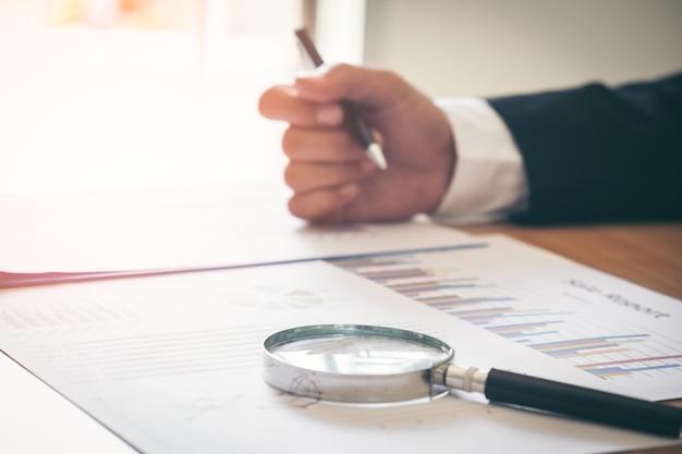 Analyse d'affaires - calculatrice, feuille, graphiques (rapport d'activité) et main d'analyste