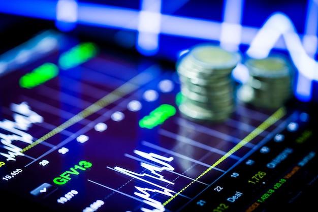 Analyse boursière avec tablette numérique avec pile de pièces