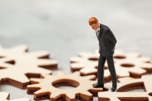 Analyse commerciale. audit de l'entreprise. un homme d'affaires en costume se lève sur les engrenages comme symbole des processus d'affaires dans l'entreprise