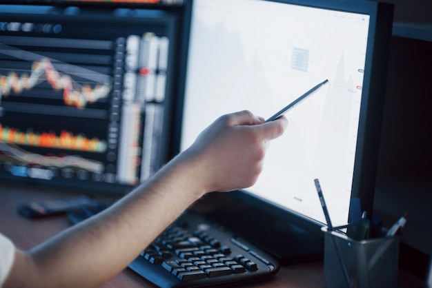 Analyse des données. gros plan du jeune homme d'affaires pointant sur les données présentées dans le graphique avec un stylo tout en travaillant au bureau de création