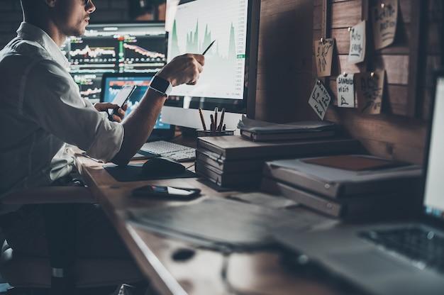Analyse des données. gros plan sur un jeune homme d'affaires regardant un moniteur assis au bureau dans un bureau de création