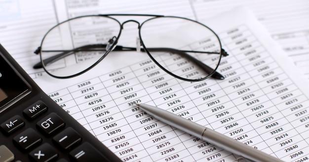 Analyse des graphiques et des graphiques financiers avec calculatrice, stylo et lunettes, entreprise