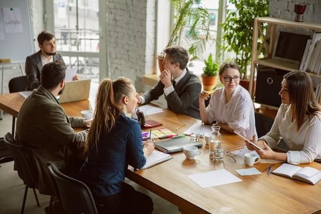 Une analyse. groupe de jeunes professionnels ayant une réunion. un groupe diversifié de collègues discute de nouvelles décisions, plans, résultats, stratégie. créativité, lieu de travail, affaires, finance, travail d'équipe.