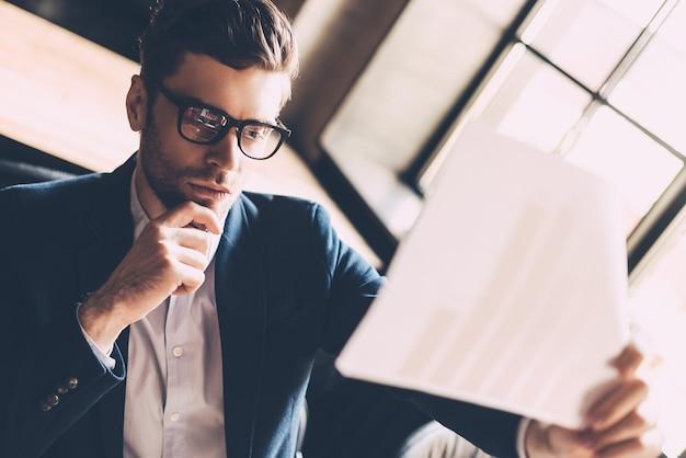 Analyser les dernières informations. gentil jeune homme en tenue décontractée intelligente tenant du papier et le regardant travailler sur un ordinateur portable alors qu'il était assis sur son lieu de travail au bureau