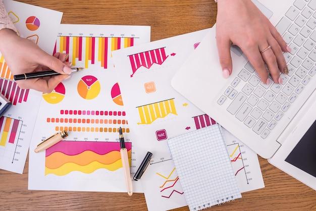 Analyste d'affaires travaillant avec des diagrammes avec un stylo et un ordinateur portable