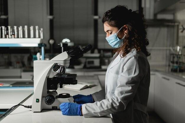 Analyste femme portant un masque protecteur en regardant le microscope.