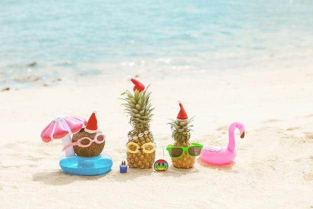 Ananas attrayants drôles et noix de coco dans des lunettes de soleil élégantes sur le sable contre la mer turquoise. porter des chapeaux de noël.
