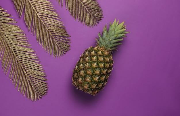 Ananas aux feuilles de palmier dorées sur fond violet. concept tropical. vue de dessus