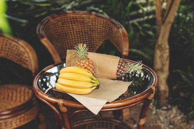 Ananas et bananes sur une table en verre de rotin au milieu de la végétation tropicale