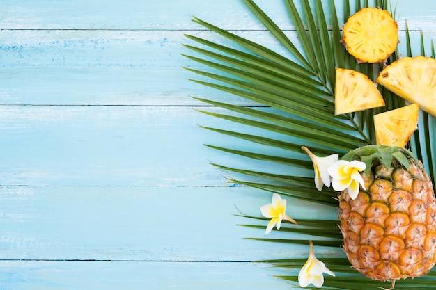 Ananas et branche de palmier sur planche de bois de couleur bleue.