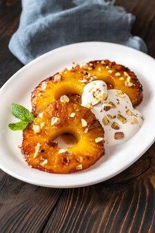 Ananas caramélisé avec chantilly et pistaches sur l'assiette de service