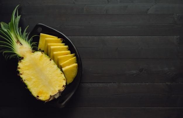 Ananas coupé dans un bol noir sur un fond en bois foncé