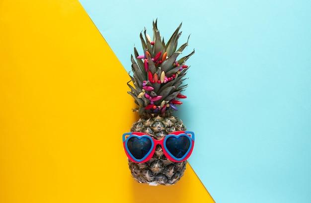 Ananas dans des lunettes de soleil en forme de coeur sur fond moitié bleu et moitié jaune