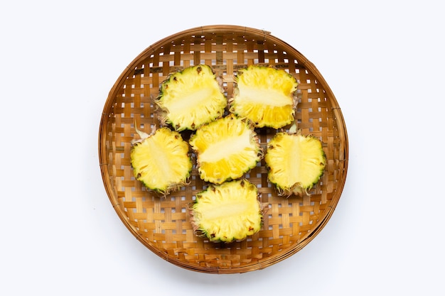 Ananas dans un panier en bambou sur fond blanc.