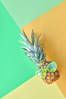 Ananas drôle dans des lunettes de soleil en forme de coeur sur du papier de couleur pastel géométrique je