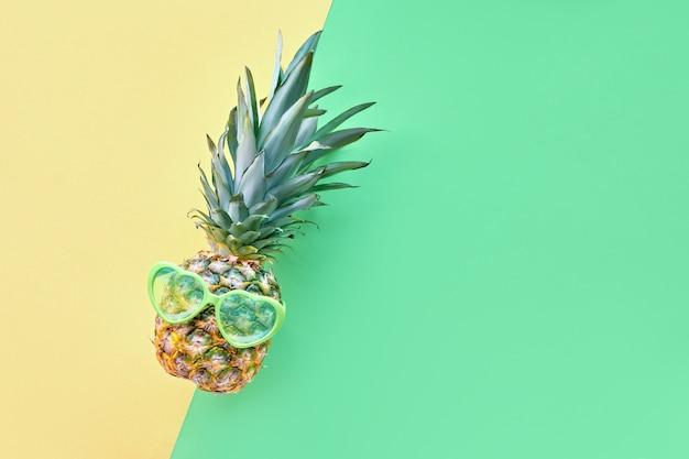 Ananas drôle en lunettes de soleil en forme de coeur sur fond de papier géométrique