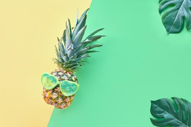 Ananas drôle en lunettes de soleil en forme de coeur sur papier géométrique avec des feuilles exotiques