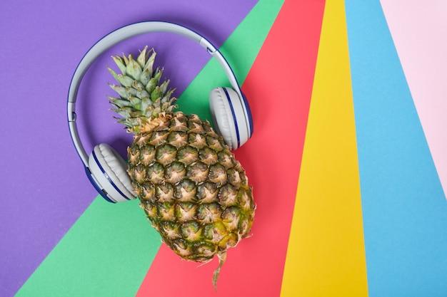 Ananas avec des écouteurs sur un fond coloré avec espace de copie, vue de dessus
