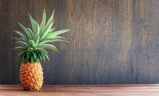 Ananas entier frais sur fond de bois, espace copie