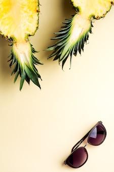 Ananas frais coupé en deux parties, cahier ou carnet de croquis et lunettes de soleil sur fond jaune. notion d'été. mise à plat créative avec espace de copie. vue de dessus