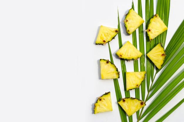Ananas frais sur des feuilles de palmier tropical sur une surface blanche